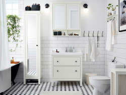 A white restroom with tiles, wash-stand and large closet with mirror home. Combined with a white wash-basin and a wall cabinet with mirror doorways.